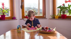 Kid painting egg on big kitchen table 4K Stock Footage