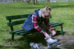 Stock Video Footage of Girl sitting on the bench and wearing rollerblades