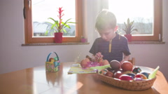 Sun shining on boy drawing on eggs 4K Stock Footage