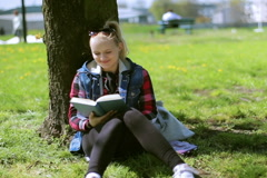 Girl sitting in the park and reading book Stock Footage