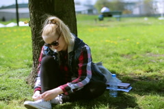 Girl sitting in the park and tying shoe laces Stock Footage