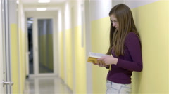 Female student reading book on corridor 4K Stock Footage