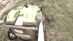 A lawn mower mowing tall grass in the lawn dreamy Stock Footage