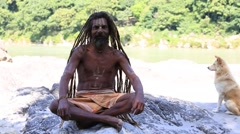 Sadhu, holy man sits on the ghat along the Ganges river.  Rishikesh, India Stock Footage