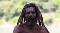 Stock Video Footage of Sadhu, holy man sits on the ghat along the Ganges river.  Rishikesh, India