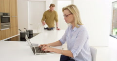 Attractive woman works from home as husband makes dinner in contemporary - stock footage