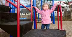 Little girl climbing up play equipment - stock footage