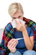Sick blonde woman blowing her nose and checking the thermometer Stock Photos