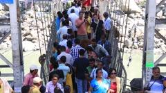 People crossing Laxman Jhula footbridge on river Ganga in Rishikesh Stock Footage