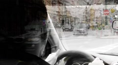 A man drives a car - urban street with passing cars:people - black and white Stock Footage