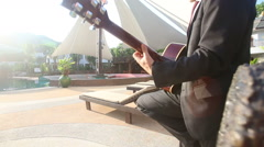 Blonde man in black suit and sunglasses plays guitar Stock Footage