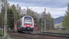 Passenger train passing old abandoned station at Minnesund Norway - stock footage
