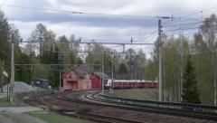 Passenger train passing old abandoned station at Minnesund Norway Stock Footage