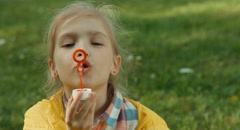 Closeup portrait child blowing soap bubbles and laughing at the camera Stock Footage