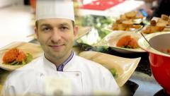 Stock Video Footage of chef smiles to camera - cooked food in the kitchen (salmon) - ready for service