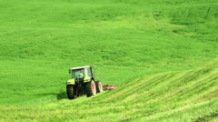 Tractor mows the green grass in spring day Stock Footage