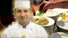 Stock Video Footage of chef smiles to camera - chef prepared food (meal: pasta) - waiter carries meals