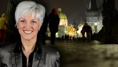 Business middle aged woman smiles - night city (buildings)-night charles bridge Stock Footage