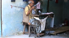 Video 1920x1080  Indian street tailor working on a foot sewing machine Stock Footage