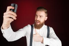 Cheerful young man with beard making selfie Stock Photos