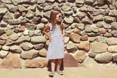 Summer, vacation, travel and people concept - little girl child in striped dr - stock photo