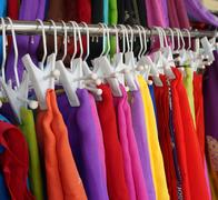 Row of colourful clothes hanging on iron railing - stock photo