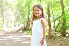 Portrait of smiling little girl walking in the forest, sunny summer day Stock Photos