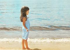 Pretty little girl walking on the beach near sea, summer, vacation, travel -  - stock photo
