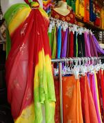 Stock Photo of Rows of colourful clothes hanging at market