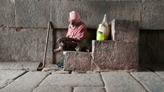 Portrait of Indian man in colorful clothes sitting on the stone stairs in Hampi. Stock Footage
