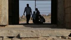Indian men passing thru the gate in Hampi. Stock Footage