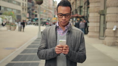 Young African Asian man in city walking texting cell phone - stock footage
