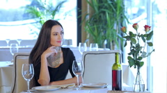 Woman seated at a table waiting for her man - stock footage
