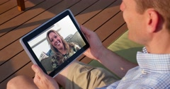 Man Video Chats with Woman on Tablet PC Outside - stock footage