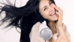 Smiling beautiful girl drying long gorgeous black hair slow motion tracking s - stock footage