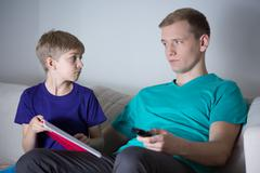 Son asks his father for help - stock photo