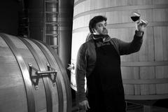 Winemaker tasting wine amongst oak casks. - stock photo