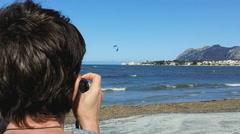 Woman shooting kite surfers on Port de Pollenca's beach - stock footage