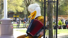 Funny man in duck mask playing accordion Stock Footage
