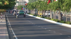 cyclists motorcyclists  buses drive along road divided by palms - stock footage