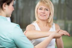 Physical therapist diagnosing painful arm Stock Photos