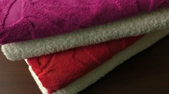 Three terry multi-coloured towels on a table Stock Footage