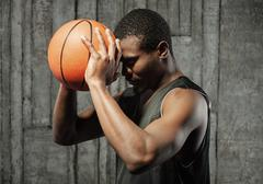 Afro-american basketball player pressing ball to his forehead - stock photo