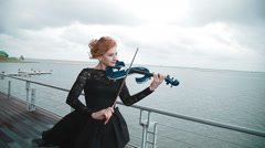 Young woman  playing the violin on the wharf. Steadicam shot Stock Footage