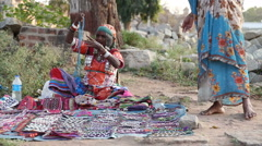 Indian woman sitting on the ground and selling her goods. Stock Footage