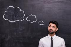 Businessman looking at cloud formed dialog on chalkboard - stock photo