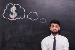 Sad businessman with dollar sign painted on chalkboard Stock Photos
