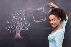 Young afro-american woman watering dollar tree painted on chalkboard - stock photo