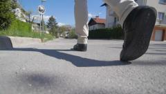 Slow motion of a man feet walking on a sunny road Stock Footage
