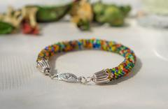 Knitted bracelet from small multi-colored beads close up Stock Photos